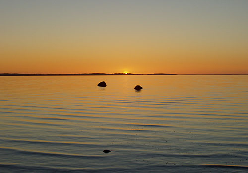 Aurinko painuu mailleen Kumpuniemen taa.